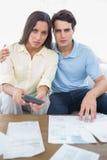 Couples inquiétés faisant leurs comptes images stock