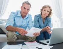 Couples inquiétés payant leurs factures en ligne avec l'ordinateur portable regardant photos stock