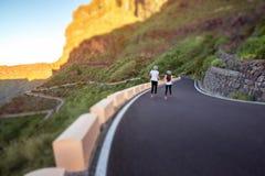 Couples insouciants fonctionnant sur le bord de la route de montagne Image libre de droits