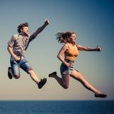 Couples insouciants sautant par l'eau d'océan de mer Photographie stock