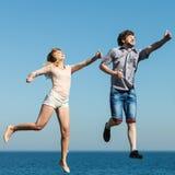 Couples insouciants sautant par l'eau d'océan de mer Photographie stock libre de droits