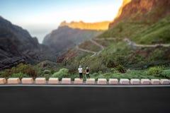 Couples insouciants se tenant sur le bord de la route de montagne Images libres de droits