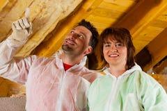 Couples installant l'isolation thermique pour couvrir Photographie stock libre de droits