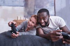 Couples internationaux amusés jouant des jeux vidéo à la maison Photos stock