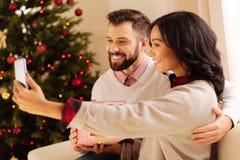 Couples internationaux heureux prenant des selfies sur Noël Photos stock