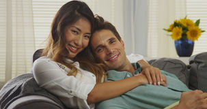 Couples interraciaux attrayants se reposant sur le divan images stock