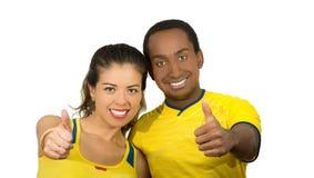 Couples interraciaux avec du charme utilisant les chemises jaunes du football donnant des pouces jusqu'à l'appareil-photo, fond b Images stock