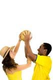 Couples interraciaux avec du charme utilisant les chemises jaunes du football tenant la boule en air entre l'un l'autre, angle de Photos libres de droits