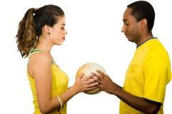 Couples interraciaux avec du charme utilisant les chemises jaunes du football tenant la boule entre l'un l'autre, studio de blanc Photographie stock libre de droits