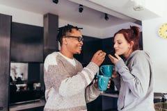 Couples interraciaux ayant le café ensemble dans le matin Images stock