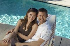 Couples interraciaux détendant ensemble sur la chaise longue Images stock