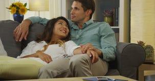 Couples interraciaux détendant sur le divan images libres de droits