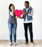 Couples interraciaux de sourire heureux tenant un coeur rouge Images stock