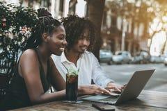Couples interraciaux des amis dans la barre dehors avec le netbook Photo libre de droits