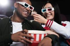 couples interraciaux en verres 3d mangeant du maïs éclaté tout en observant le film Image libre de droits