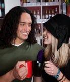 Couples interraciaux grillant avec des cuvettes de café Images stock