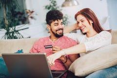 Couples interraciaux heureux faisant des emplettes en ligne à la maison Photos libres de droits