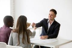 Couples interraciaux heureux obtenant des clés à la nouvelle maison de l'agent immobilier image libre de droits