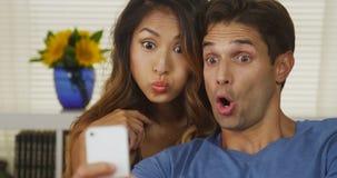 Couples interraciaux heureux prenant des autoportraits Image libre de droits