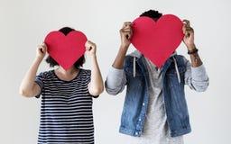 Couples interraciaux heureux tenant les icônes rouges de coeur Photos stock