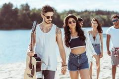 Couples interraciaux tenant des mains et passant le temps avec leurs amis sur la plage Photo libre de droits