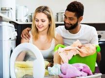Couples interraciaux utilisant la machine à laver Photos stock
