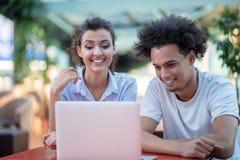 Couples interraciaux utilisant la tablette dans le caf? photographie stock