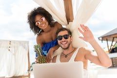 Couples jeunes heureux dans l'amour communiquant par le carnet sur la plage Images libres de droits