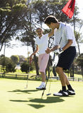Couples jouant au golf Photos libres de droits