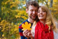 Couples jouant avec la feuille en parc d'automne Photo stock