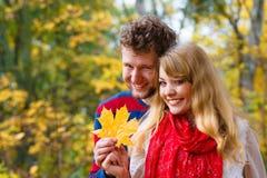 Couples jouant avec la feuille en parc d'automne Images libres de droits