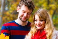 Couples jouant avec la feuille en parc d'automne Photographie stock