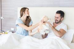 Couples jouant avec le jouet de peluche Photos libres de droits