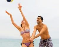 Couples jouant avec une boule à la plage Photo stock