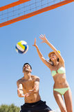 Couples jouant avec une boule au bord de mer Image libre de droits