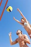 Couples jouant avec une boule et sauter Photographie stock libre de droits