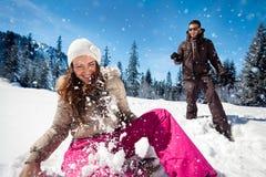 Couples jouant dans la neige Photographie stock