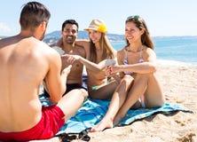 Couples jouant des cartes sur la plage Photo libre de droits
