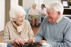 Couples jouant des dominos au centre de soins de jour Photographie stock libre de droits