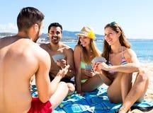 Couples jouant des jeux de carte sur la plage Photographie stock libre de droits