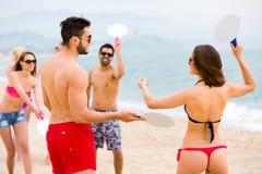 Couples jouant des jeux sur une plage Image libre de droits