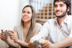Couples jouant des jeux vidéo sur le divan Photos stock