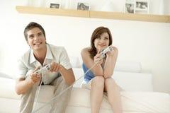 Couples jouant des jeux vidéo sur le sofa Photo libre de droits