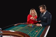 Couples jouant des victoires de roulette au casino Photo stock