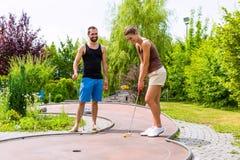 Couples jouant ensemble le golf miniature dehors Image libre de droits