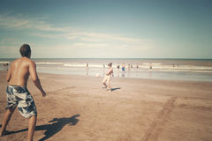 Couples jouant la boule dans une plage Photos libres de droits