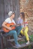 Couples jouant la guitare acoustique et le chant Photographie stock libre de droits