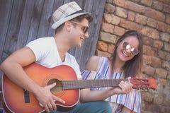 Couples jouant la guitare acoustique et le chant Images libres de droits