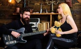 Couples jouant la guitare et se reposant à la maison Le concept de détendent des vacances Équipez la guitare de jeu tandis que la Photos libres de droits