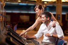 Couples jouant la machine à sous Photographie stock libre de droits
